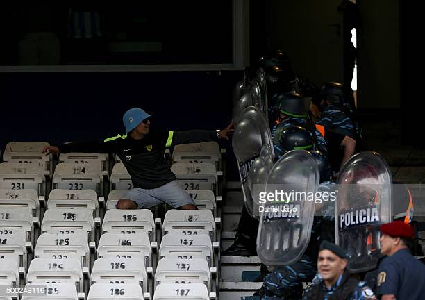 A fan of Racing Club clashes with police officers during a second leg match between Independiente and Racing Club as part of Pre Copa Libertadores...