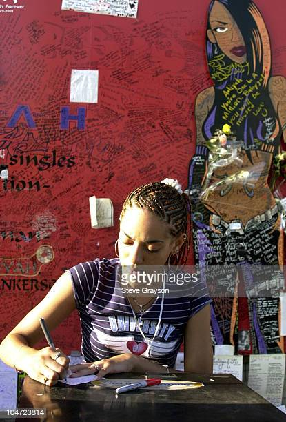 A fan of RB singer/actress Aaliyah signs a note to post on at a record store mural of the late singer in what has become a shrine dedicated to her...