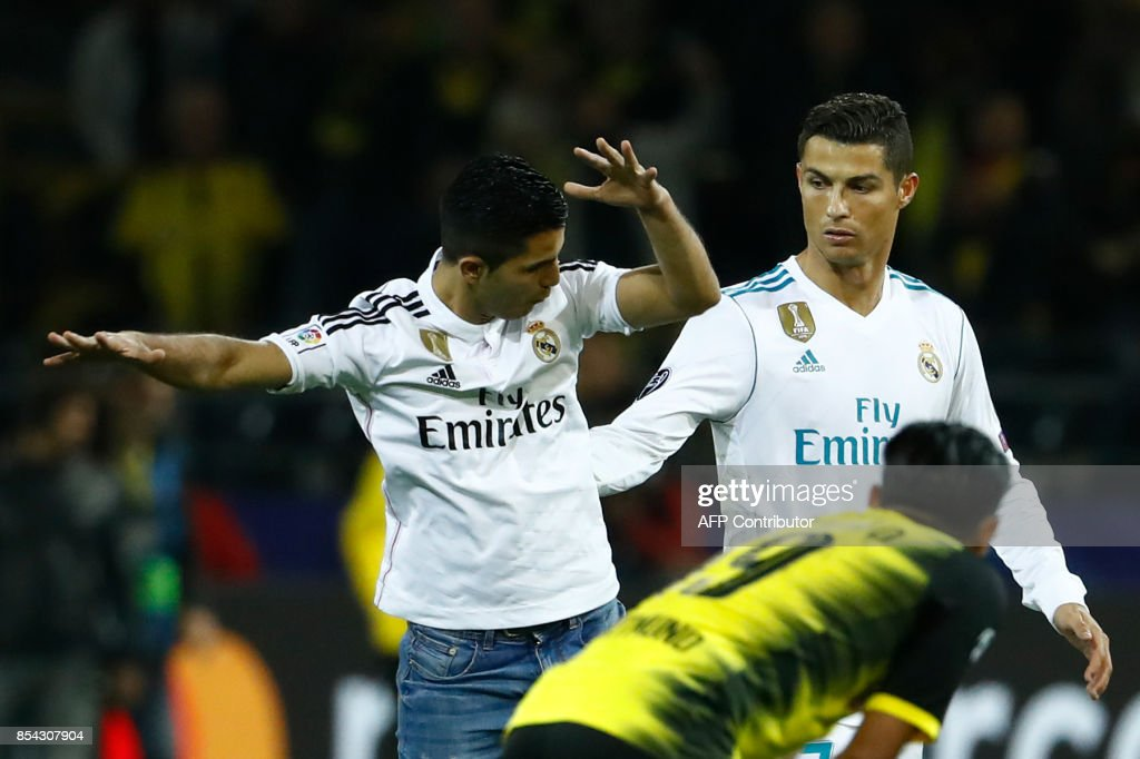A fan (L) of Real Madrid's forward from Portugal Cristiano Ronaldo (R) jumps next to his hero after the UEFA Champions League Group H football match BVB Borussia Dortmund v Real Madrid in Dortmund, western Germany on September 26, 2017. / AFP PHOTO / Odd ANDERSEN
