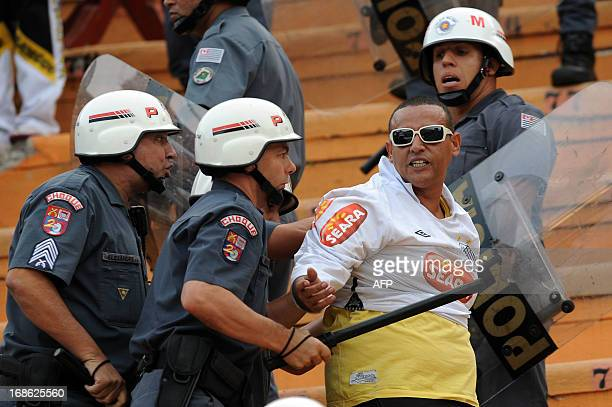 A fan of Santos FC is taken from the stands by the police before the 2013 Paulista championship first leg football final against Corinthians held at...