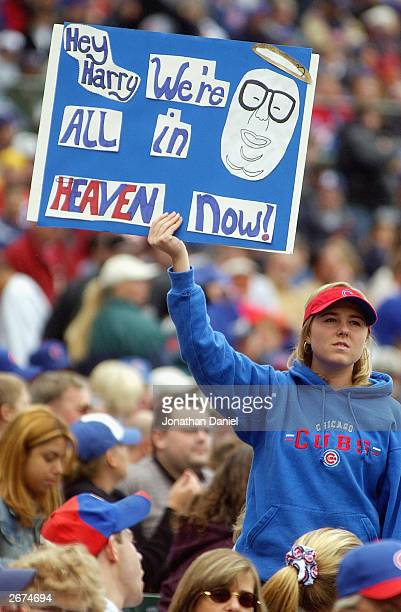 A fan of the Chicago Cubs holds a sign refering to former Cub announcer Harry Caray during a game against the Pittsburgh Pirates on September 28 2003...