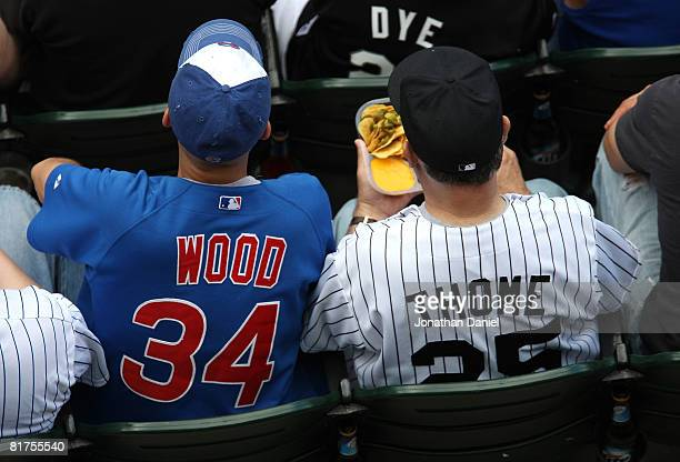 A fan of the Chicago Cubs wearing a Kerry Wood jersey sits next to a fan of the Chicago White Sox wearing a Jim Thome jersey at US Cellular Field on...
