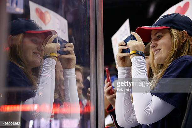 A fan of the Columbus Blue Jackets takes pictures with her phone during pregame warmups prior to the start of the game between the Columbus Blue...