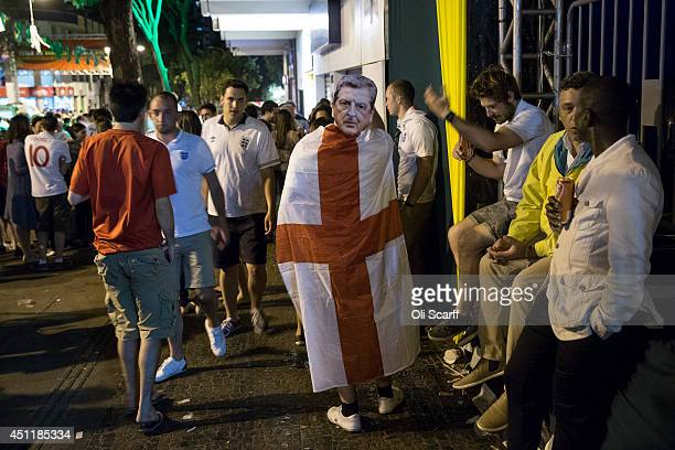 A fan of the England football team wears a Union Flag and a mask of the England Manager Roy Hodgson outside a bar in the centre of Belo Horizonte...