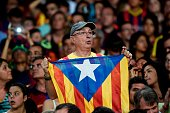 A fan of the FC Barcelona holds a Catalan independentist flag 'Estelada' as he waits for his team to celebrate their victory over Juventus one day...