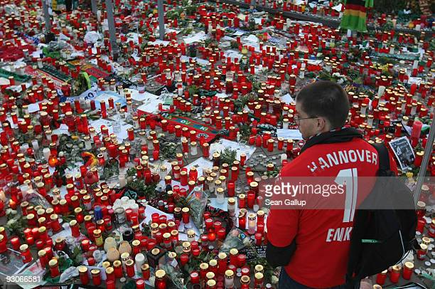 A fan of the Hannover 96 football club looks at a sea of candles for goalie Robert Enke shortly before a memorial service prior to Enke�s funeral at...