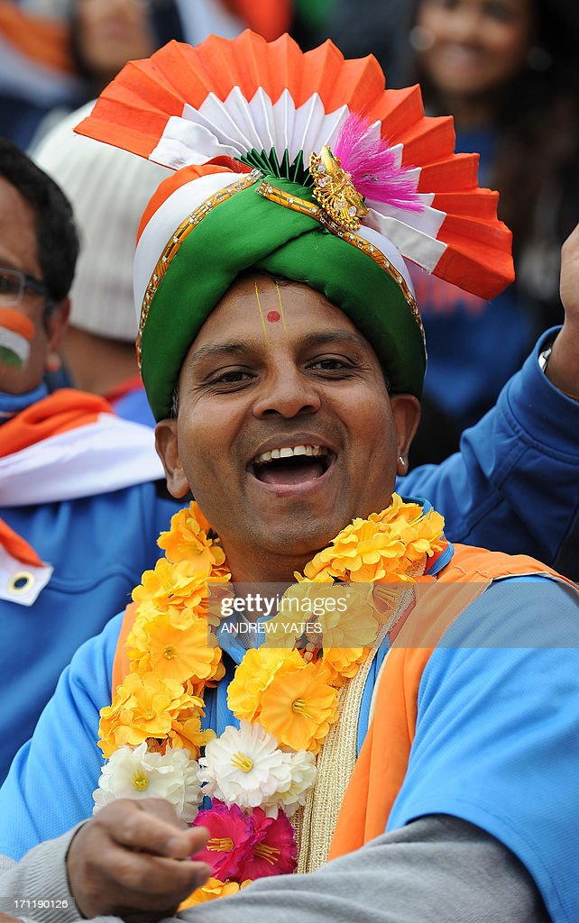 A fan of the Indian cricket team, wearing a turban in the team's colours, smiles as rain interupts the start of the 2013 ICC Champions Trophy Final cricket match between England and India at Edgbaston in Birmingham, central England on June 23, 2013.
