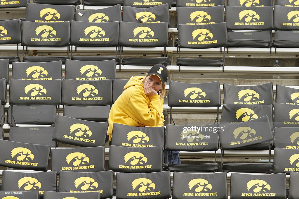 A fan of the Iowa Hawkeyes sits alone in an empty section following the match-up against the Michigan State Spartans on October 5, 2013 at Kinnick Stadium in Iowa City, Iowa. Michigan State won 26-14.