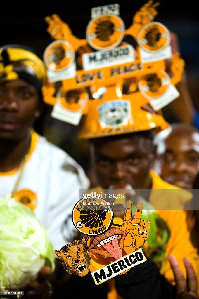 A fan of the Kaizer Chiefs wearing a makarapa a customised miner's hard hat / fan helmet and blowing a vuvuzela trumpet horn