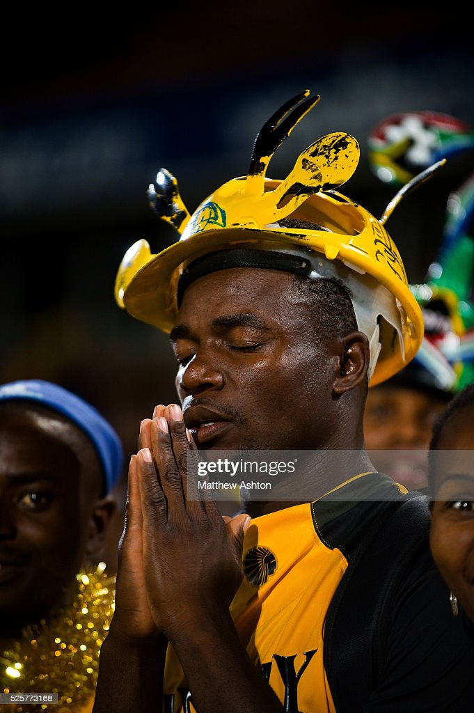 A fan of the Kaizer Chiefs wearing a makarapa a customised miner's hard hat / fan helmet preying for a victory