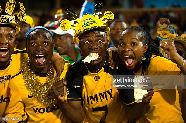 A fan of the Kaizer Chiefs wearing a makarapa a customised miner's hard hat / fan helmet and eating a cabbage