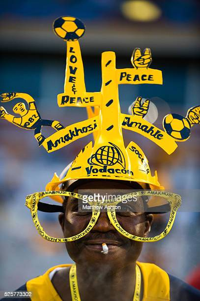 A fan of the Kaizer Chiefs wearing a makarapa a customised miner's hard hat / fan helmet and a pair of glasses whilst smoking