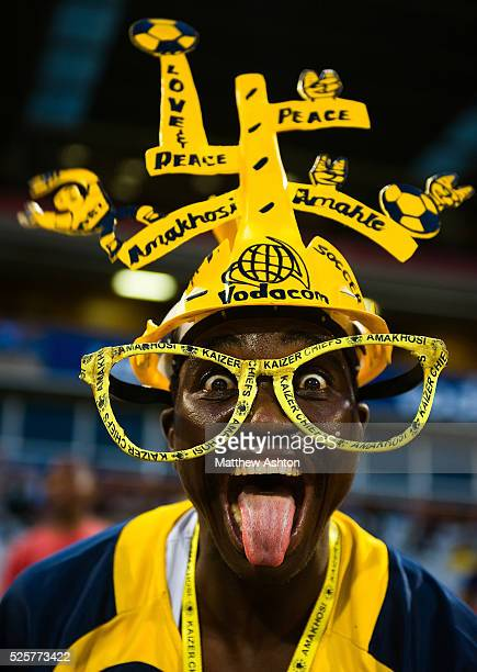 A fan of the Kaizer Chiefs wearing a makarapa a customised miner's hard hat / fan helmet wearing glasses