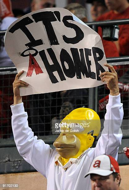 A fan of the Los Angeles Angels of Anaheim dressed as 'Homer Simpson' hold a sign in support of the Angels during Game Two of the ALDS against the...