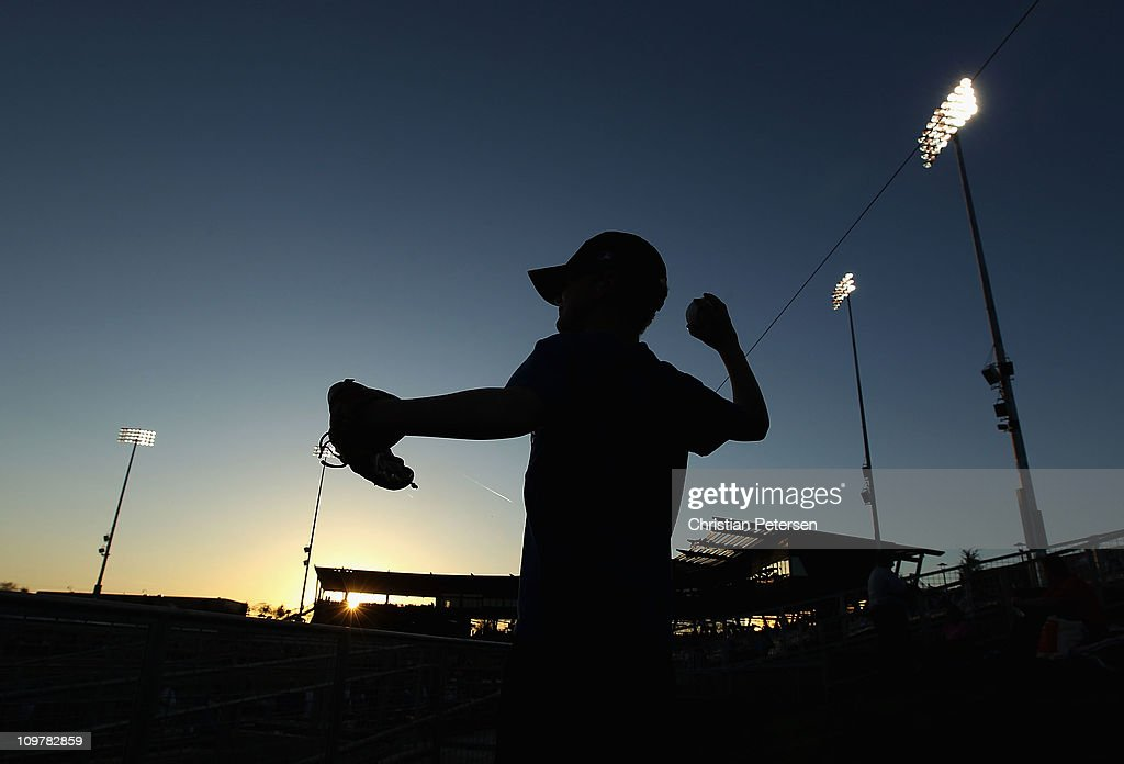 A fan of the Los Angeles Dodgers plays catch in the outfield before the spring training game against the San Francisco Giants at Camelback Ranch on March 4, 2011 in Glendale, Arizona.