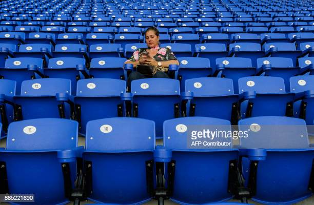 A fan of the National Baseball Team of Nicaragua looks at her phone before the friendly game of the National Baseball Team of Nicaragua against the...