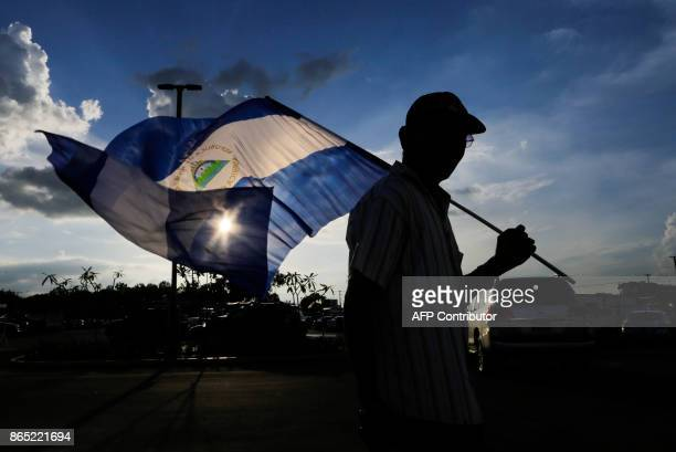 A fan of the National Baseball Team of Nicaragua walks with a flag of Nicaragua before the friendly game of the National Baseball Team of Nicaragua...