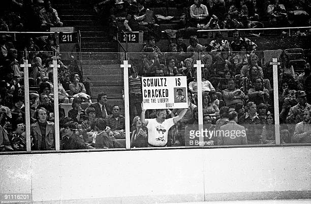 A fan of the New York Islanders holds a sign showing his displeasure for Dave Schultz of the Philadelphia Flyers as the sign reads 'Schultz is...