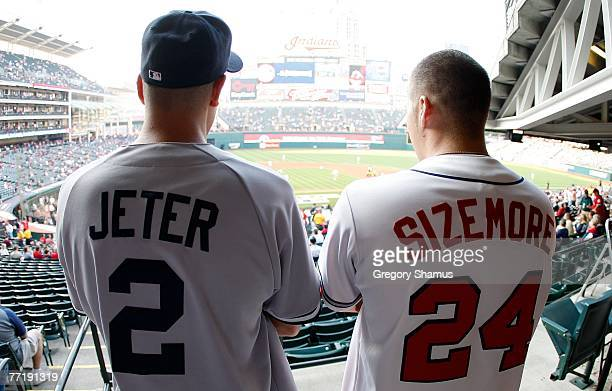 A fan of the New York Yankees wearing a Derek Jeter jersey and a fan of the Cleveland Indians wearing a Grady Sizemore jersey look down towards the...