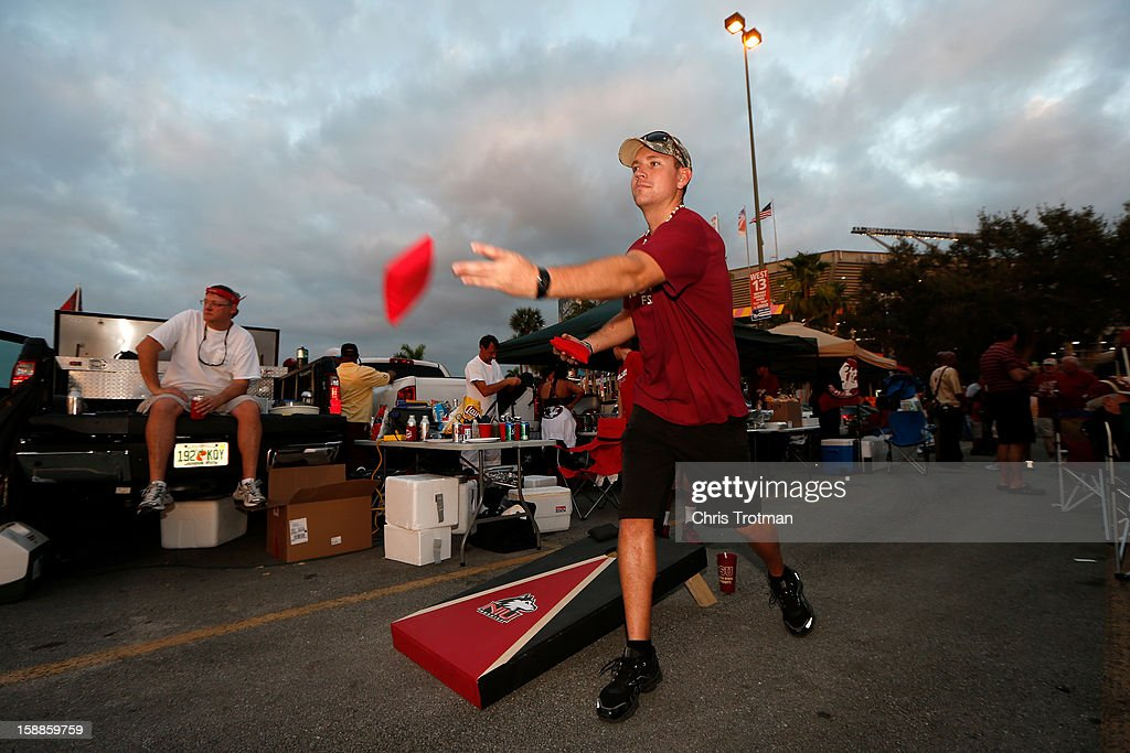A fan of the Northern Illinois Huskies plays a bean bag toss game in the parking lot prior to watching the Huskies play the Florida State Seminoles during the Discover Orange Bowl at Sun Life Stadium on January 1, 2013 in Miami Gardens, Florida.