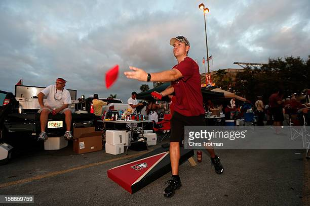 A fan of the Northern Illinois Huskies plays a bean bag toss game in the parking lot prior to watching the Huskies play the Florida State Seminoles...