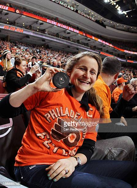 A fan of the Philadelphia Flyers shows off her game used puck against the Toronto Maple Leafs on February 9 2012 at the Wells Fargo Center in...