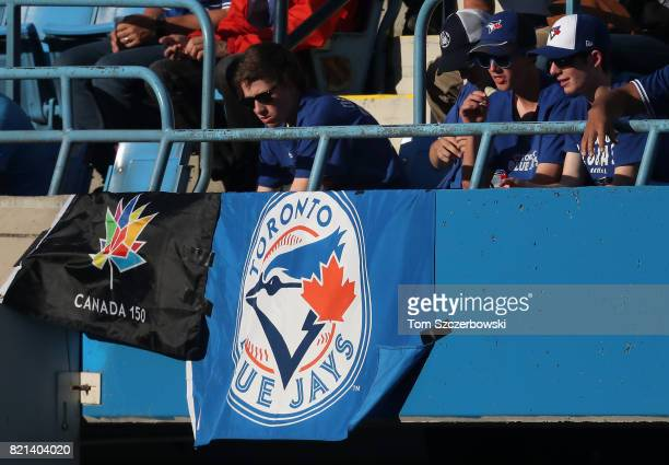 A fan of the Toronto Blue Jays hangs a flag celebrating the 150th anniversary of Canada from the facing of the upper deck during MLB game action...