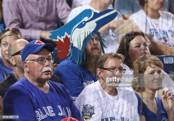 A fan of the Toronto Blue Jays wears a foam hat in the shape of a blue jay as he watches the game during MLB game action against the Kansas City...