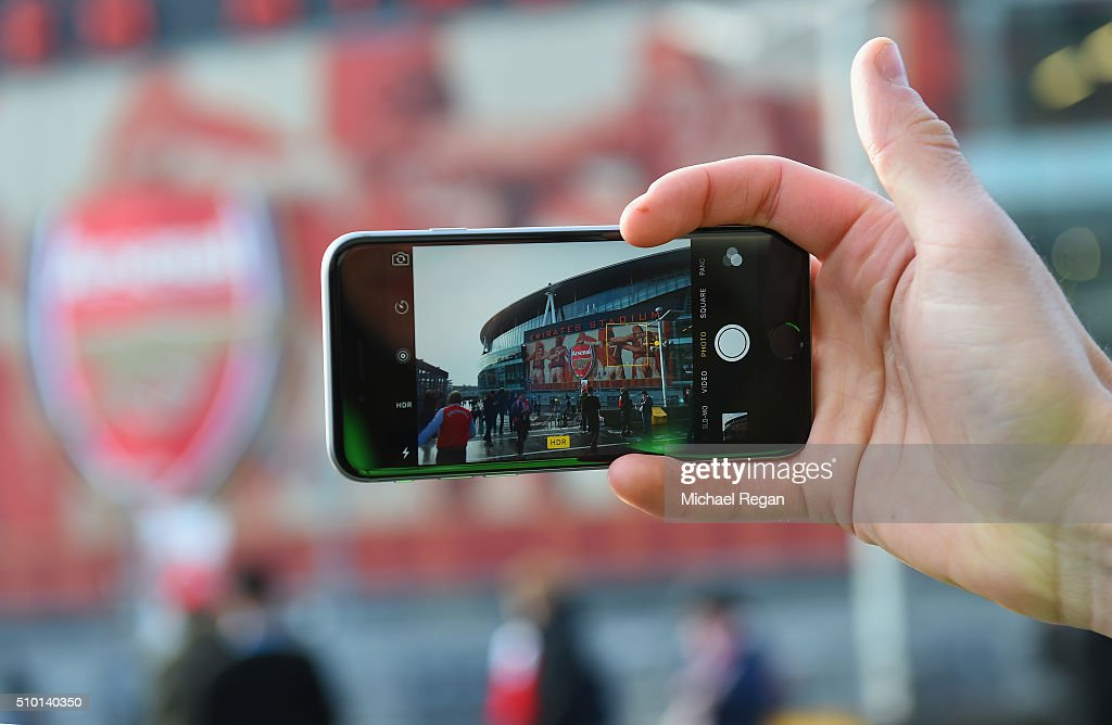 A fan photographs the stadium on his phone prior to the Barclays Premier League match between Arsenal and Leicester City at the Emirates Stadium.
