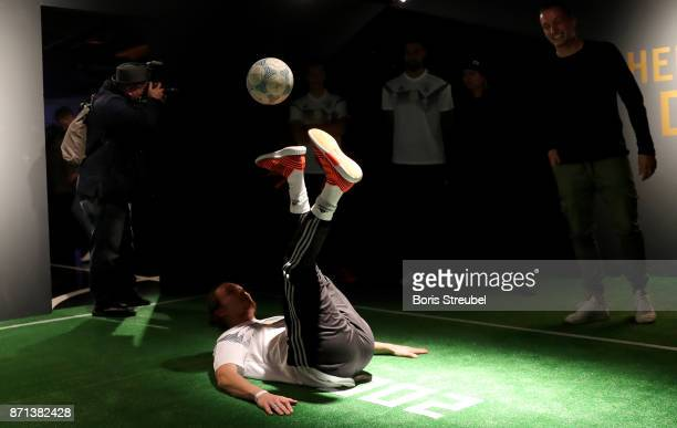 A fan plays with a football during the presentation of the 2018 FIFA World Cup Russia Adidas jersey at The Base on November 7 2017 in Berlin Germany