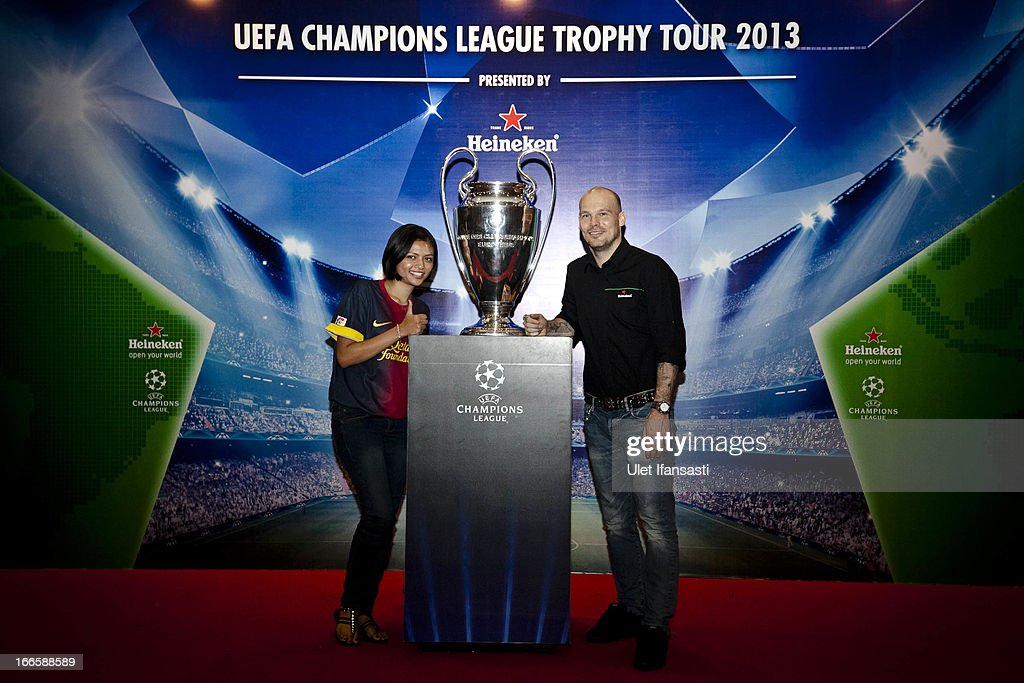A fan pose with Ambassador <a gi-track='captionPersonalityLinkClicked' href=/galleries/search?phrase=Fredrik+Ljungberg&family=editorial&specificpeople=167144 ng-click='$event.stopPropagation()'>Fredrik Ljungberg</a>, with the UEFA Champions League trophy during the UEFA Champions League Trophy Tour 2013 presented by Heineken at Gandaria City Shopping Mall on April 13, 2013 in Jakarta, Indonesia.