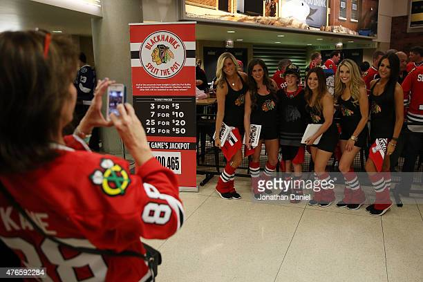 A fan poses for a photo with members of the ice crew before the start of Game Four of the 2015 NHL Stanley Cup Final between the Chicago Blackhawks...