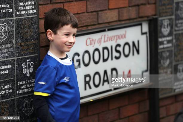 A fan poses for a photograph next to a road sign prior to the Premier League match between Everton and West Bromwich Albion at Goodison Park on March...