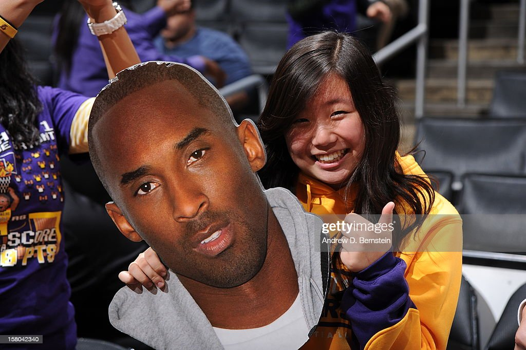 A fan poses for a photograph with the face of Kobe Bryant #24 of the Los Angeles Lakers before a game against the Utah Jazz at Staples Center on December 9, 2012 in Los Angeles, California.