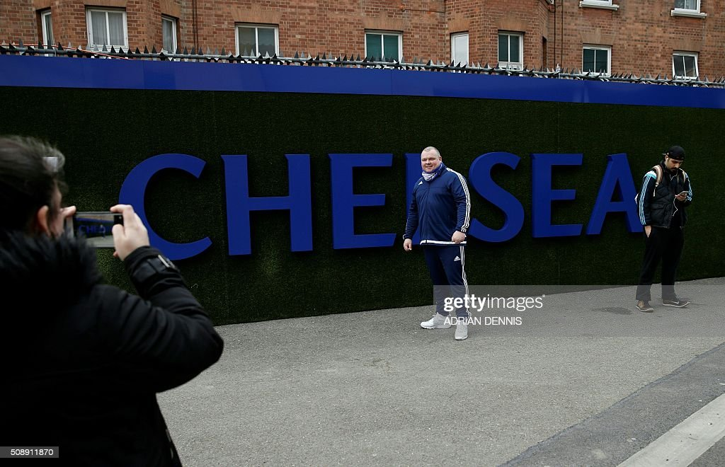 A fan poses for a picture before the English Premier League football match between Chelsea and Manchester United at Stamford Bridge in London on on February 7, 2016. / AFP / ADRIAN DENNIS / RESTRICTED TO EDITORIAL USE. No use with unauthorized audio, video, data, fixture lists, club/league logos or 'live' services. Online in-match use limited to 75 images, no video emulation. No use in betting, games or single club/league/player publications. /