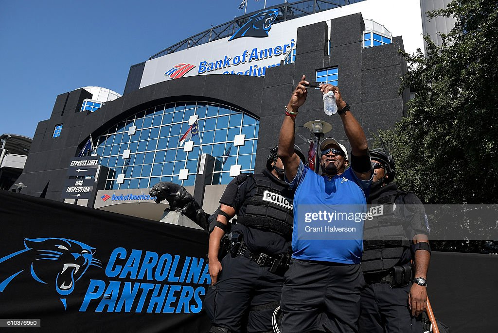 A fan poses for a portrait with Charlotte Mecklenburg Police Department officers prior to the game between the Carolina Panthers and the Minnesota Vikings at Bank of America Stadium on September 25, 2016 in Charlotte, North Carolina. Charlotte has been the site of civil unrest since Keith Lamont Scott, 43, was shot and killed by police officers at an apartment complex near UNC Charlotte.