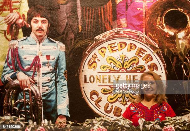 A fan poses in fornt of the famous Rhe Beatles' Sgt Pepper Lonely Hearts Club Band album cover by British photographer Michael Cooper during an...