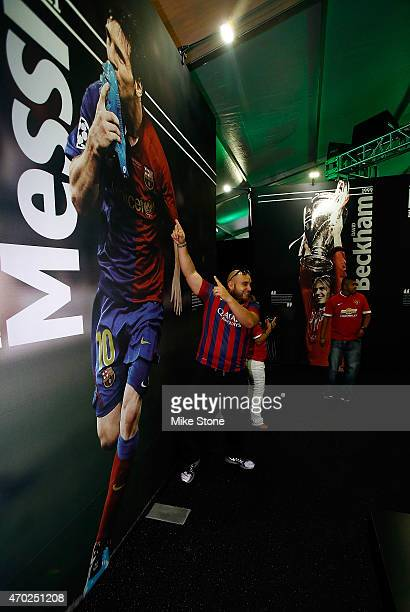 A fan poses in front of one of the wall murals at the 2015 UEFA Champions League Trophy Tour presented by Heineken exhibit on April 18 2015 in Dallas...