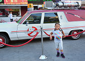 Fan poses in front of the 'Ghostbusters' Cadillac Fleetwood Station Wagon at AMC Universal City Walk on July 14 2016 in Universal City California