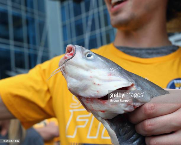A fan poses with a catfish prior to the game between the Nashville Predators and the Pittsburgh Penguins in Game Four of the 2017 NHL Stanley Cup...
