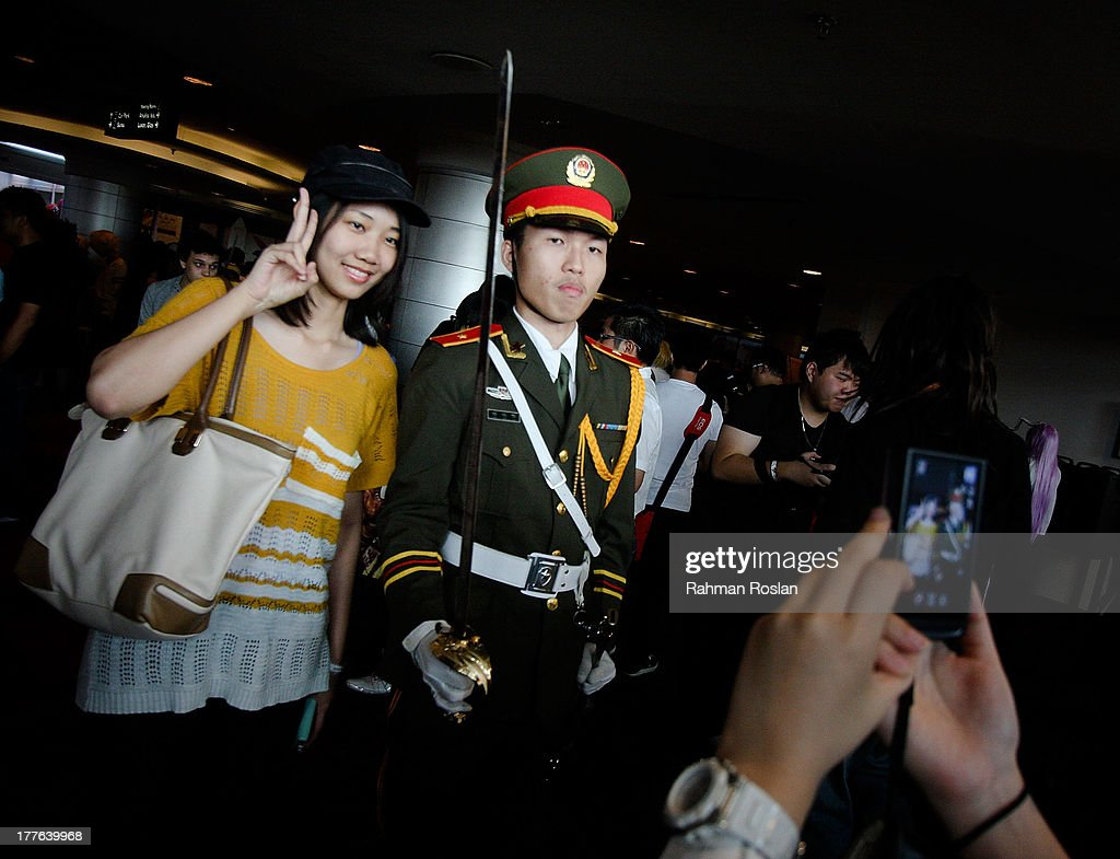 A fan poses with a Cosplayer who dresses up as an army general during the final day of AniManGaki on August 25, 2013 in Kuala Lumpur, Malaysia. AniManGaki, which is now into its fifth year, attracts fans of Anime, Manga and Cosplay from across Asia who gather together to celebrate the genre.