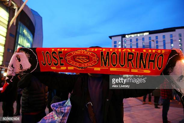 A fan poses with a Manchester United scarf displaying the image and name of former Chelsea manager Jose Mourinho outside the stadium before the...