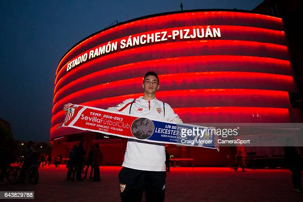 A fan poses with a match scarf outside the Estadio Ramon Sanchez Pizjuan ahead of the UEFA Champions League Round of 16 first leg match between...