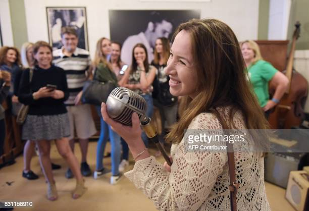 A fan poses with a microphone used by Elvis Presley during a tour of Sun Studio where Presley made his first recordings on August 13 2017 in Memphis...