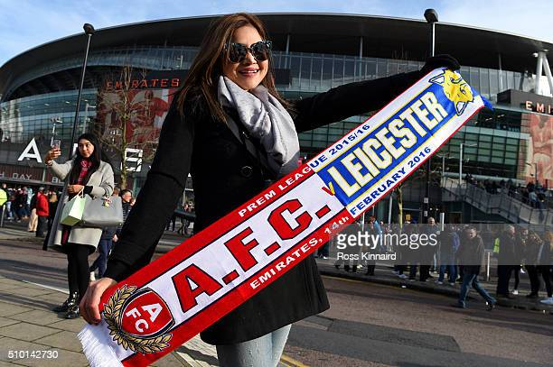 A fan poses with a scarf outoside the stadium before the Barclays Premier League match between Arsenal and Leicester City at Emirates Stadium on...