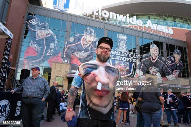 A fan poses with a shirt depicting Zach Werenski's injury prior to Game Four of the Eastern Conference First Round between the Pittsburgh Penguins...