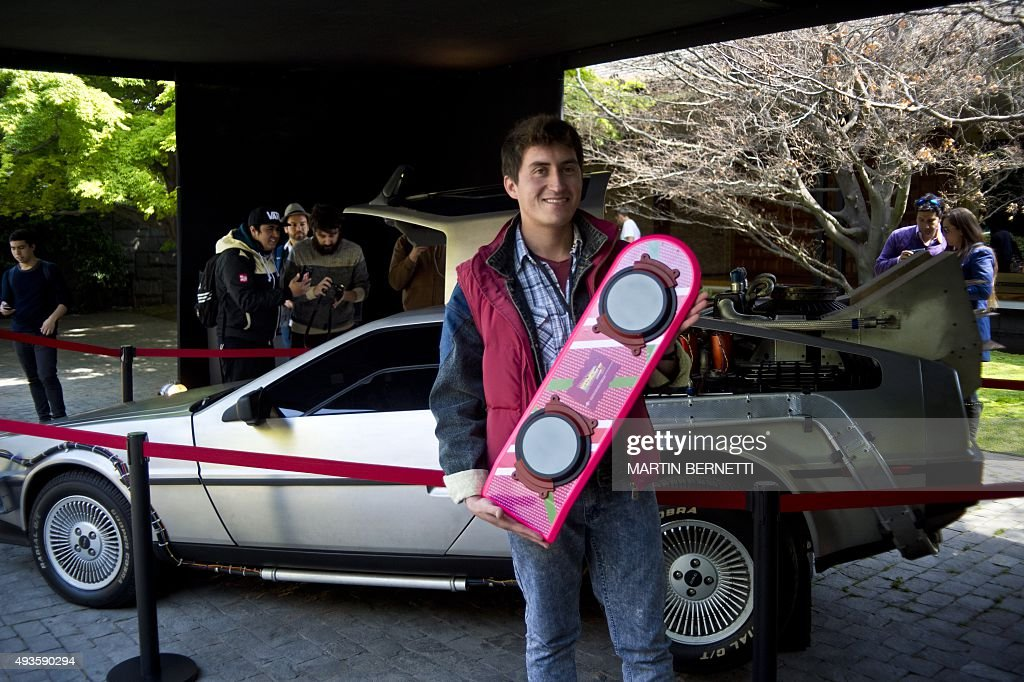 A fan poses with a skate in front of a replica of the DeLorean a timemachine vehicle which appeared in the movie ' Back to the Future'' in 1985 is...