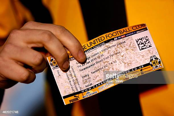 A fan poses with a ticket before the FA Cup Fourth Round match between Cambridge United and Manchester United at The R Costings Abbey Stadium on...