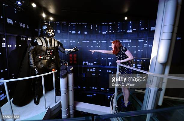 A fan poses with a wax figure of Star Wars character Darth Vader at 'Star Wars At Madame Tussauds' on May 12 2015 in London England