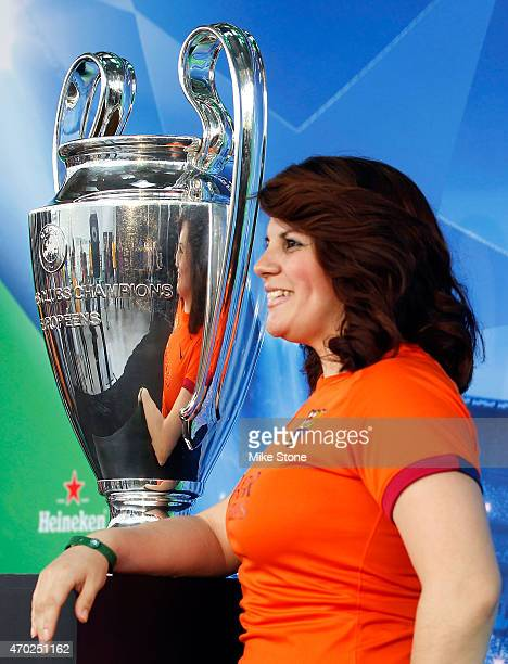 A fan poses with the Champions League Trophy at the 2015 UEFA Champions League Trophy Tour presented by Heineken exhibit on April 18 2015 in Dallas...